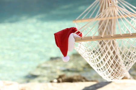 Santa claus hat on Hammock in a tropical beach resort with the sea water in the background photo