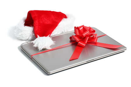 electronics equipment: Laptop computer christmas gift with a ribbon and santa hat isolated on white background