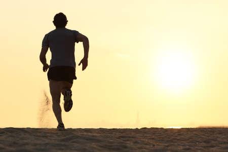 running: Volver vista de la silueta de un hombre corredor corriendo en la playa al atardecer con el sol en el fondo