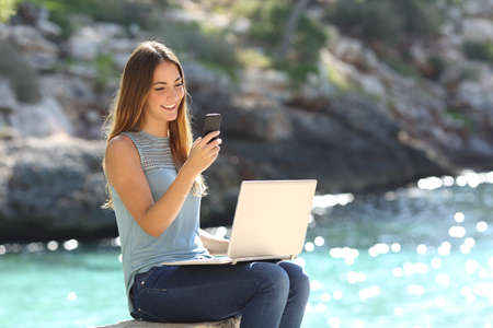 Entrepreneur working woman with a phone and a laptop on holidays in a tropical beach Stock Photo