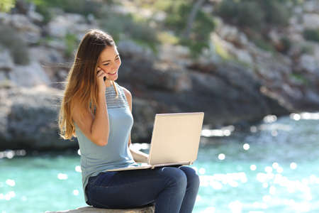 Freelance woman working in vacation on the phone on the beach with the sea in the background photo