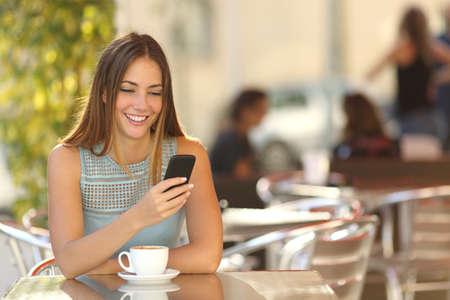 スマート電話、やり場のない背景を持つレストランのテラスで女の子のテキスト メッセージ
