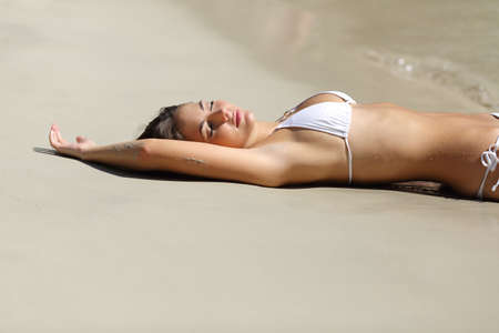 underarms: Sunbather woman showing armpit hair removal laser lying on the sand of the beach on holidays Stock Photo