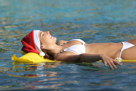 Woman enjoying on the beach on christmas holidays on a floating mattress