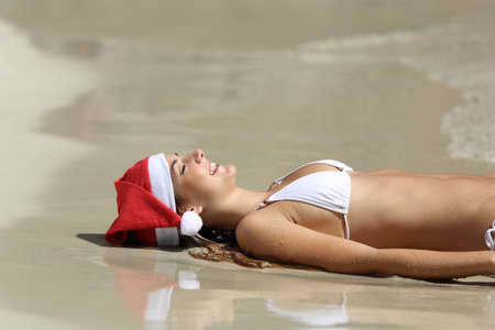 hat new year s eve: Woman resting on the sand of the beach relaxing on christmas holidays Stock Photo