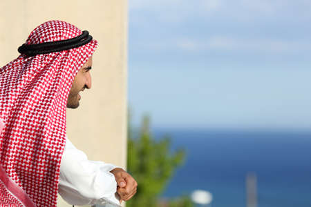 arab adult: Happy relaxed arab saudi man looking the sea from a balcony of an hotel Stock Photo