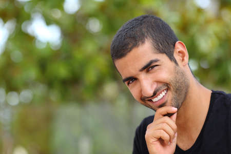 Retrato de un hermoso rostro árabe hombre al aire libre en un parque con un fondo verde