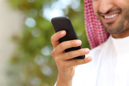 arab man: Smiling arab saudi man hand using a smart phone outdoor in a park with a green background
