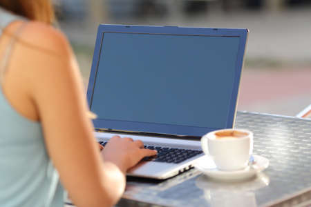 laptop: Closeup of a girl typing on a laptop and showing screen in a restaurant terrace