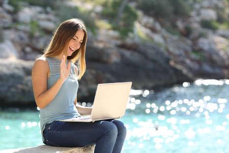 Toeristische vrouw op vakantie online te genieten met een laptop op het strand met de zee op de achtergrond