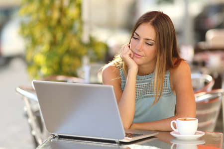 thoughtful woman: Serious woman watching a laptop in a restaurant terrace with an unfocused background Stock Photo
