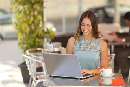 tazas de cafe: Independiente mujer o estudiante que trabaja en un restaurante con terraza en la calle con un fondo desenfocado