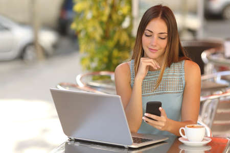 Self employed woman working with her phone and laptop in a restaurant terrace with a cup of coffee