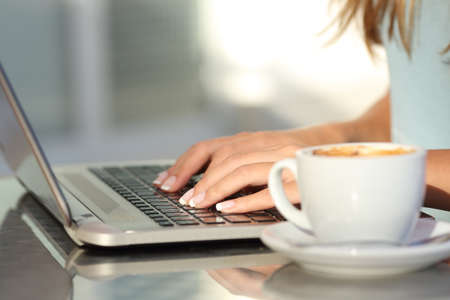 Close up of a woman hands typing in a laptop in a coffee shop terrace in the street