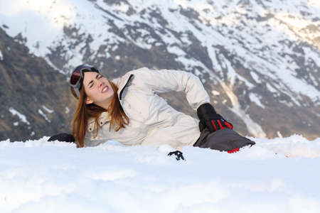 hip fracture: Skier woman hurt lying in the snow of a high mountain