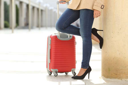 suit case: Close up of a tourist woman legs waiting with a suit case in an airport or station