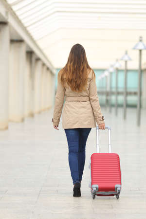 suit case: Back view of a tourist woman walking and carrying a suit case in an airport or station