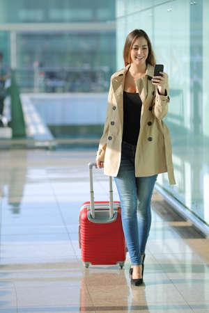 Vooraanzicht van een reiziger vrouw lopen en met behulp van een slimme telefoon in een luchthaven gang