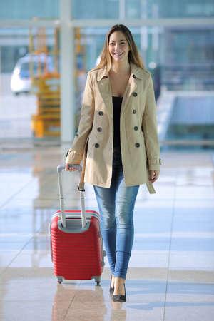 Vista frontale di una donna che viaggia a piedi una valigia in un corridoio all'aeroporto