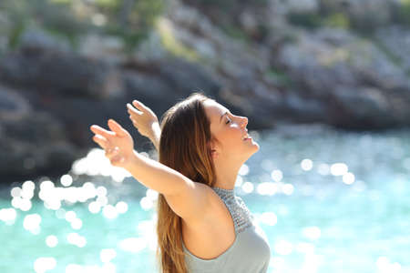 free backgrounds: Happy woman breathing fresh air raising arms on holidays with a tropical sea in the background