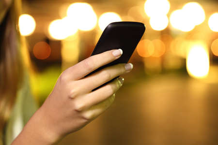 Close up of a woman hand using a smart phone in the night with lights in the background 스톡 콘텐츠