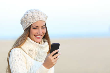 warmly: Woman warmly clothed in winter using a smart phone on the beach