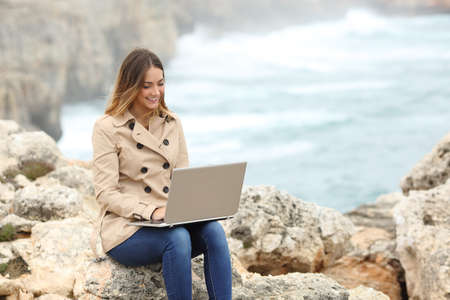 self study: Beautiful woman browsing her laptop in winter on the coast with the ocean in the background Stock Photo
