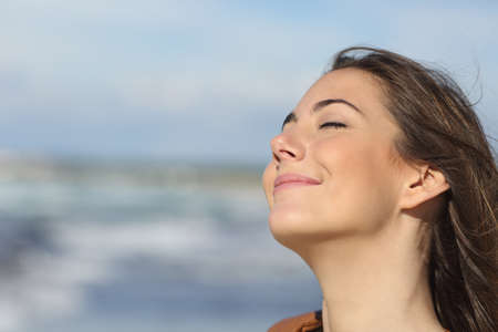 in the air: Closeup portrait of a relaxed woman breathing fresh air on the beach Stock Photo