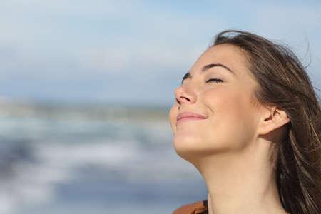 persona respirando: Primer retrato de una mujer relajada de respirar aire fresco en la playa