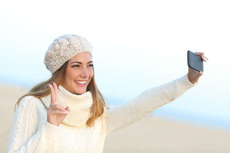 clothed: Girl taking a selfie with her smart phone warmly clothed in winter on the beach Stock Photo
