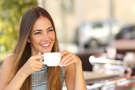 Gelukkig peinzende vrouw denken in een coffeeshop terras in de straat