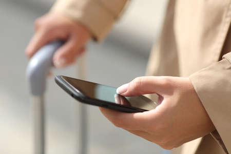 Close up of a traveler woman hand consulting a smartphone and holding a suit case photo