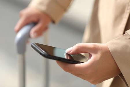 Close-up van een reiziger vrouw de hand raadpleging van een smartphone en houden van een koffer