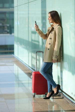 persona de pie: Los viajeros de pie mujer usando un tel�fono inteligente y esperando en un aeropuerto con una maleta con un fondo de cristal verde Foto de archivo