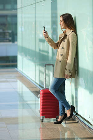 Traveler standing woman using a smart phone and waiting in an airport with a suitcase with a green glass background