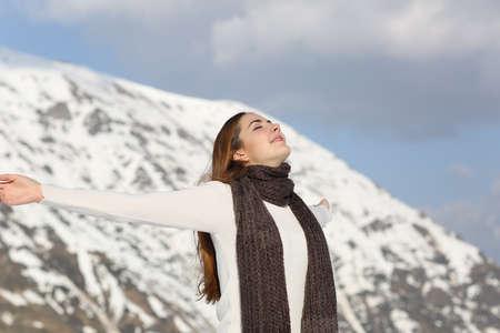 女性の冬の雪に覆われた山を背景に腕を上げて新鮮な空気を呼吸 写真素材