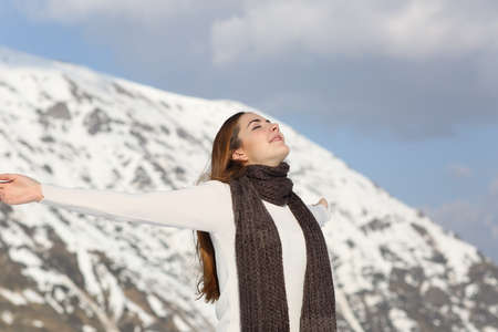 winter woman: Woman breathing fresh air raising arms in winter with a snowy mountain in the background Stock Photo