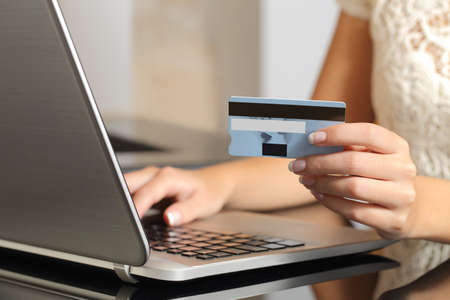 Close up of a woman hands buying online with a credit card and a laptop. Ecommerce concept photo