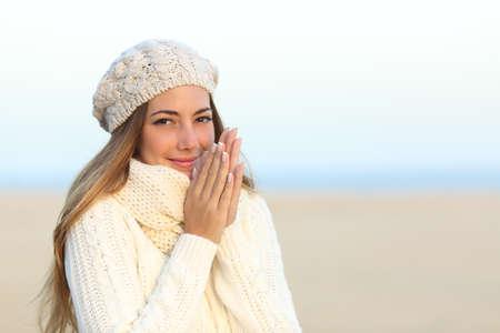 Vrouw van harte gekleed in een koude winter op het strand met de hemel op de achtergrond Stockfoto
