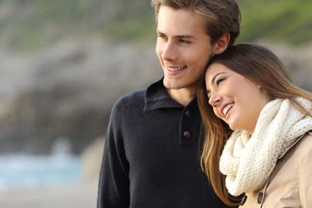 finding a mate: Affectionate couple looking away and hugging on the beach Stock Photo