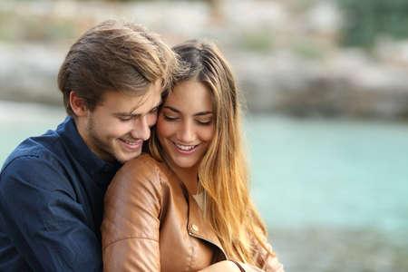 amour couple: Couple c�lins affectueux sur la plage en hiver avec la mer en arri�re-plan Banque d'images