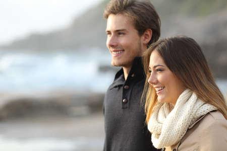 mujer mirando el horizonte: Vista lateral de una pareja en invierno que mira lejos en la playa al atardecer Foto de archivo