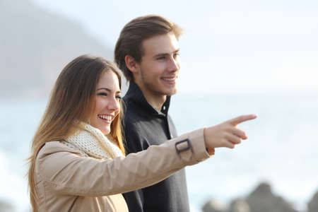 Couple looking forward on the beach and pointing at side with an unfocused background photo