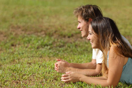 finding a mate: Profile of a couple lying on the grass and looking away with a green background
