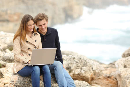 Couple sharing a laptop on the beach on winter holidays with the ocean in the background photo