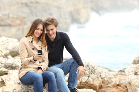 Couple sharing a smart phone on the beach on winter holidays with the ocean in the background photo