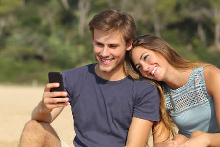 Happy teenager couple sharing social media on the smart phone outdoors Stock Photo