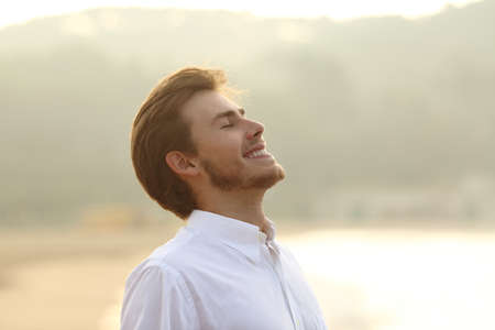 respiracion: Hombre feliz de respirar profundo en la playa en vacaciones con un fondo amarillo aislado en blanco por encima de Foto de archivo