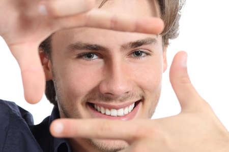 front teeth: Man with perfect white smile framing face with hands on a white background