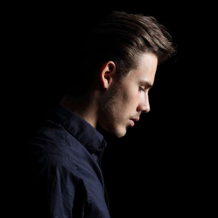 see side: Profile of a sad man face crestfallen on black isolated on a black background